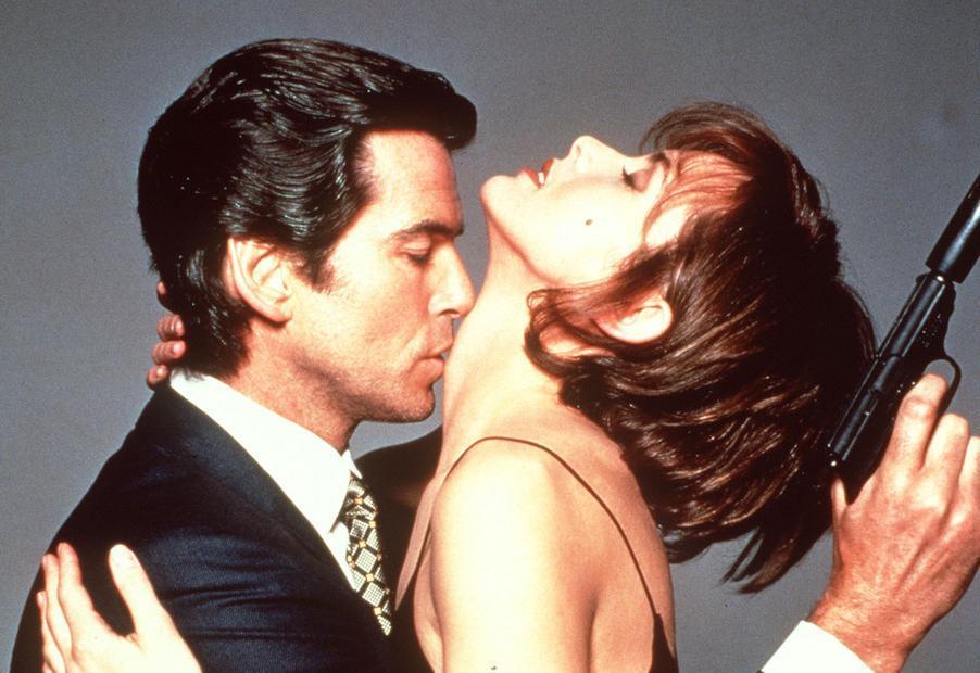 Mann med pistol kysser kvinne på halsen. Foto.