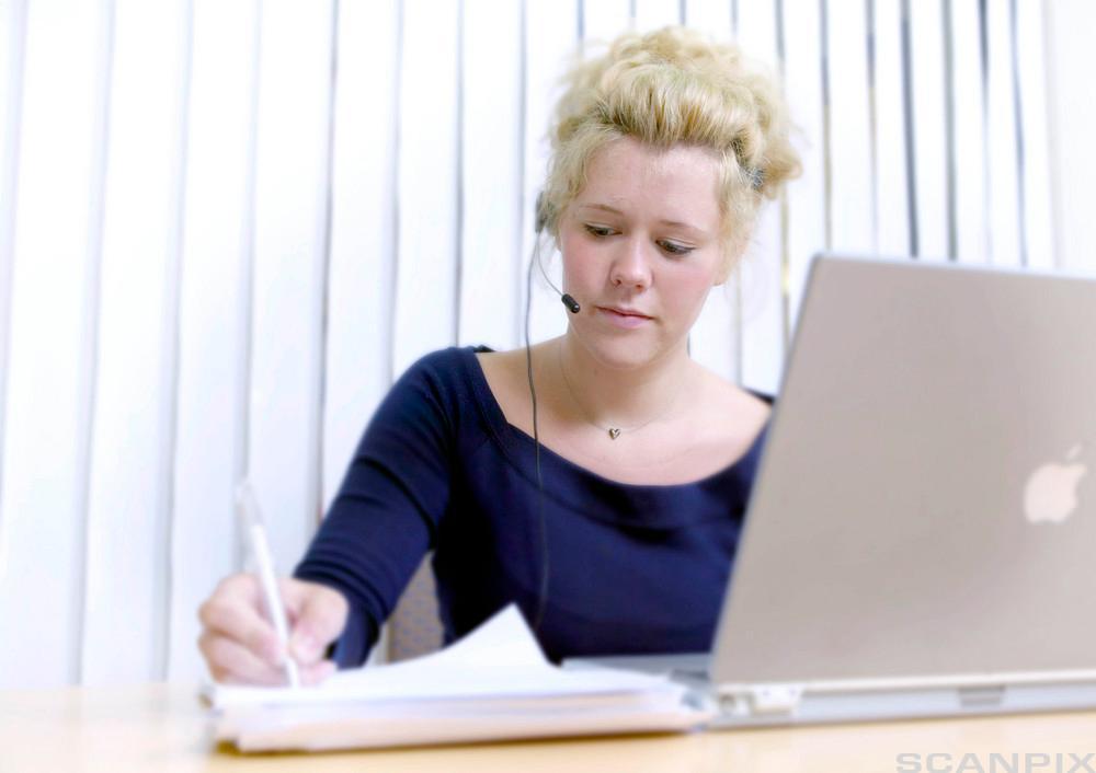 Bilete av ei kvinne med hovudtelefonar og datamaskin.