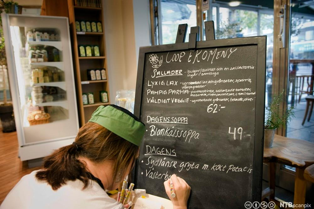 Kokk skriv opp dagens økologiske meny på ei tavle. Foto.