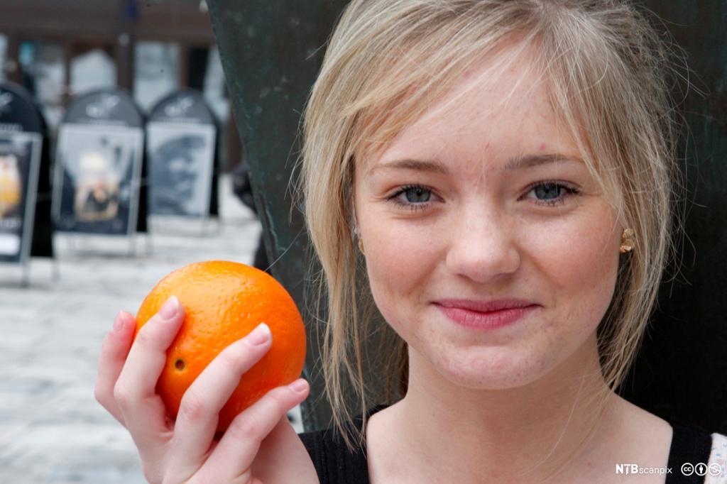 Jente holder en appelsin. Foto.