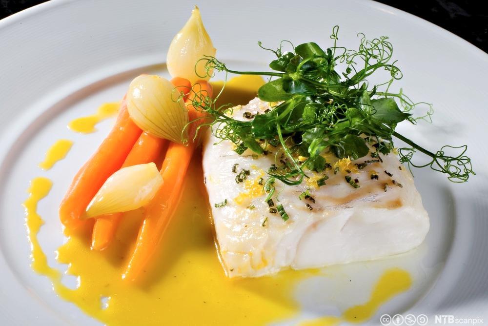 Bakt torskefilet på ein tallerken med appelsin og ingefærkokte gulrøter. Foto.