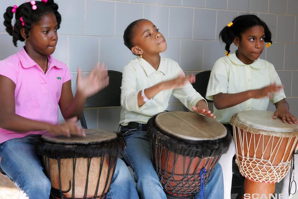 Barn som spiller djembetrommer. Foto.