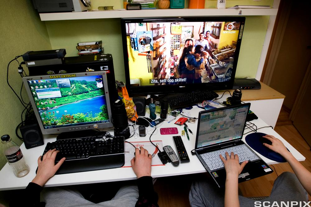 Barn bruker ulike digitale enheter på et rom. Foto.