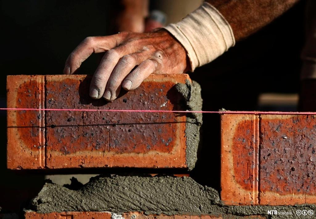 Hender som murer med rød murstein. Foto.