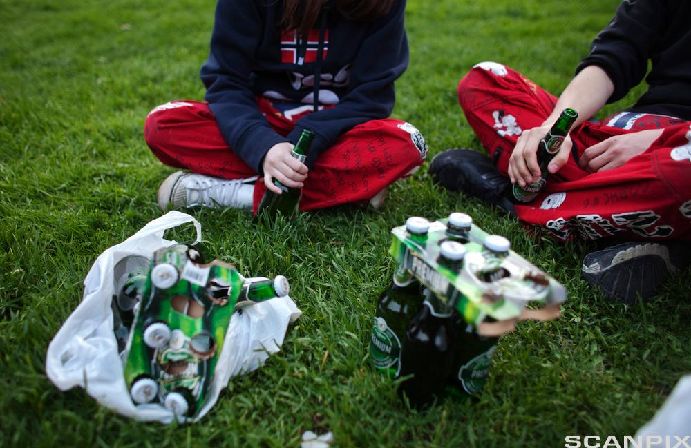 Russ sitter på gress med ølflasker rundt seg. Foto.