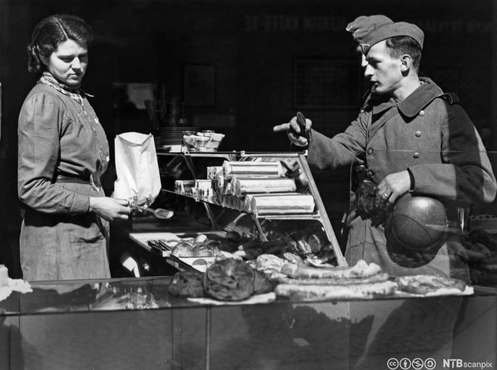 Tyske soldater gjør innkjøp i bakerforretning, og blir ekspedert av ung kvinne. Ansiktsutrykket hennes røper at hun ikke er veldig innstilt på å yte service.