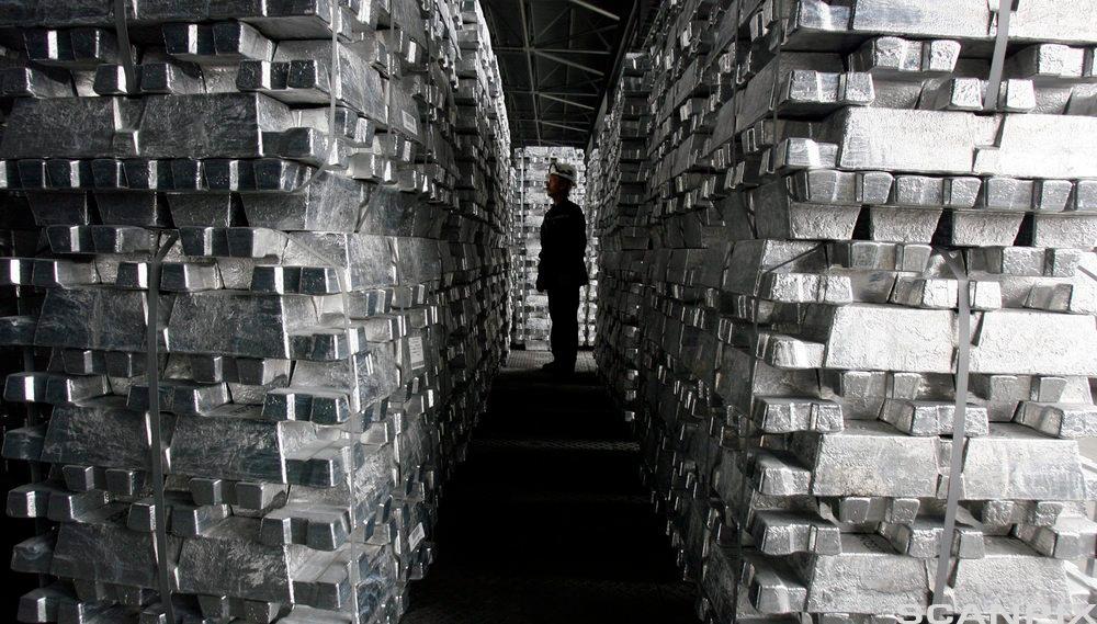 n arbeidstaker går mellom stabler av blokker i ren aluminium. foto.