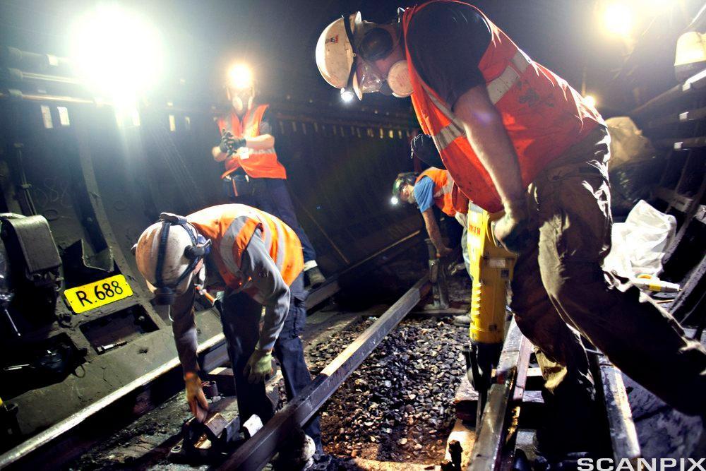 Tre personer arbeider ved jernbaneskinner. Foto.