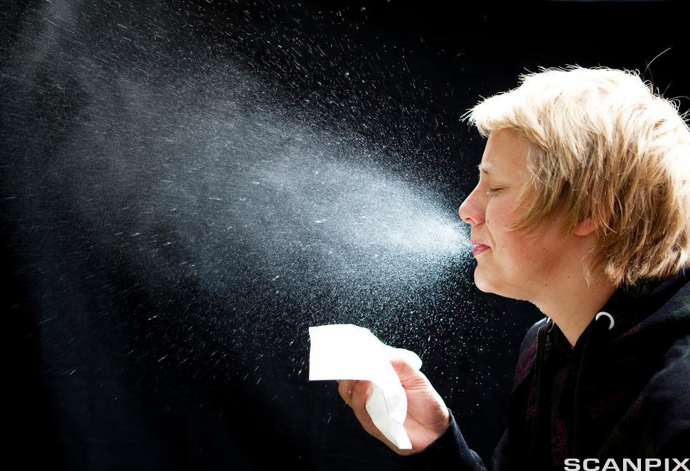 Kvinne som nyser og en sky av dråper kommer ut av munnen hennes. Foto
