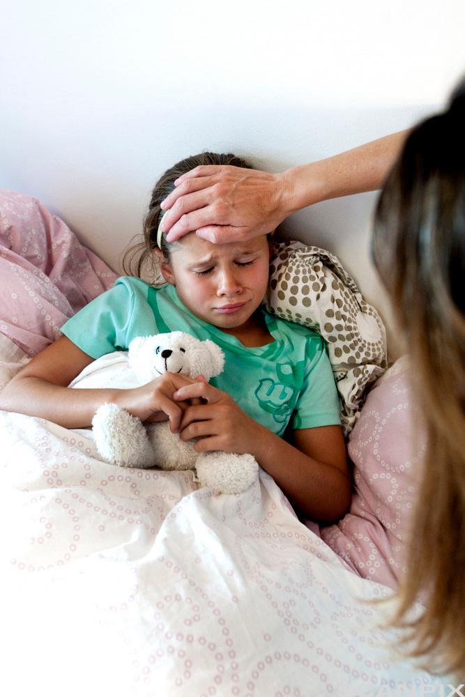 Bildet viser ei jente som er syk og ligger i senga