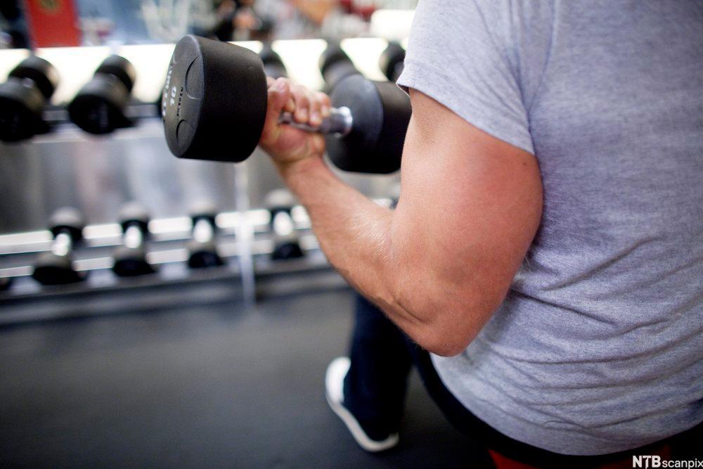 Person løfter vekter på et treningssenter. Foto.