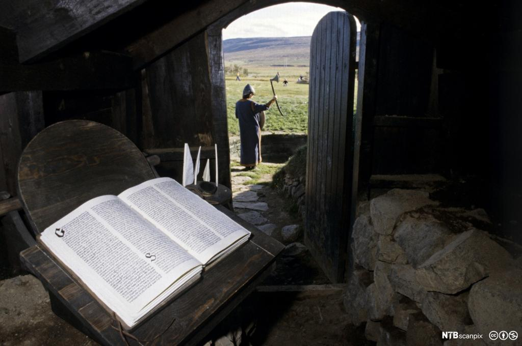 Utsikt fra underjordisk gang til islandsk landskap og mann med hjelm. I forgrunnen en oppslått bok. Foto.