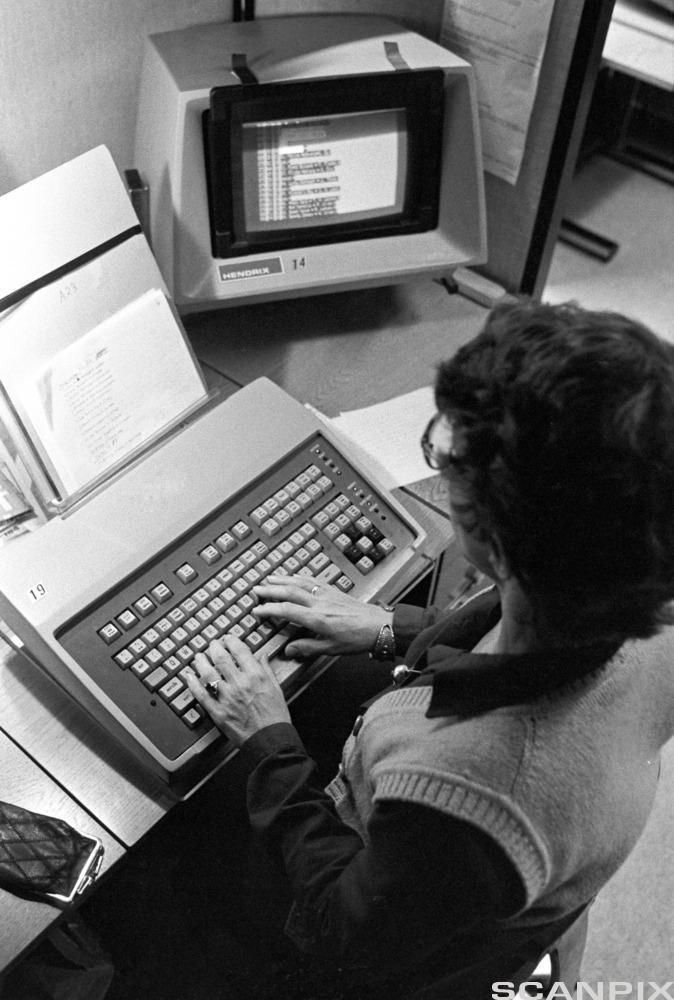 Kvinne som skriver på gammel datamaskin. Foto.