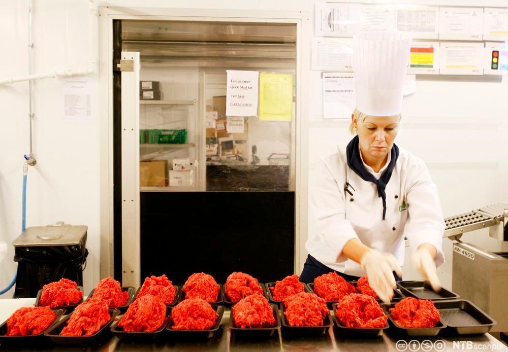 En kokk porsjonerer kjøttdeig i engansbegere. Foto.