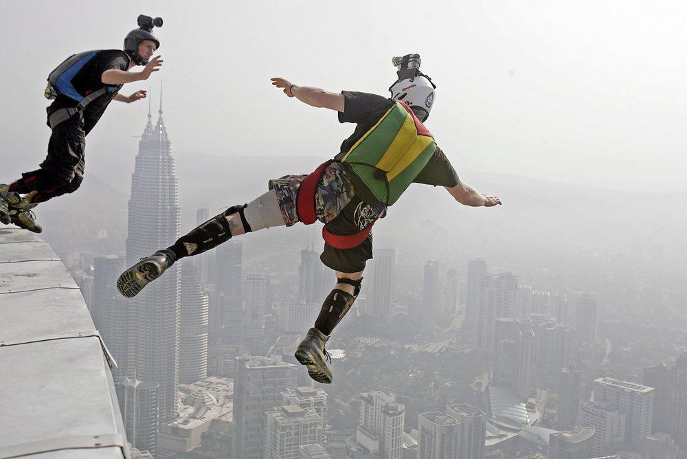 To personer hopper fra taket på en skyskraper.