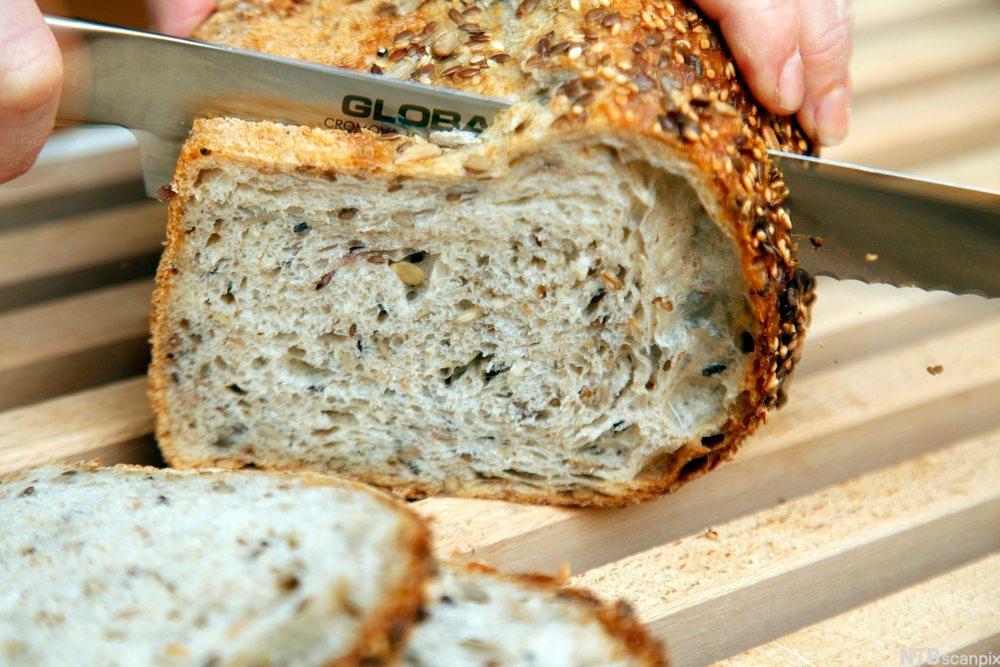 Ett brød som skjæres opp i skiver. Foto.