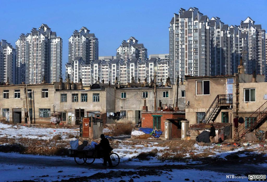 Nye skyskrapere reiser seg i bakgrunnen av et eldre boligkvarter i Kina. Foto.