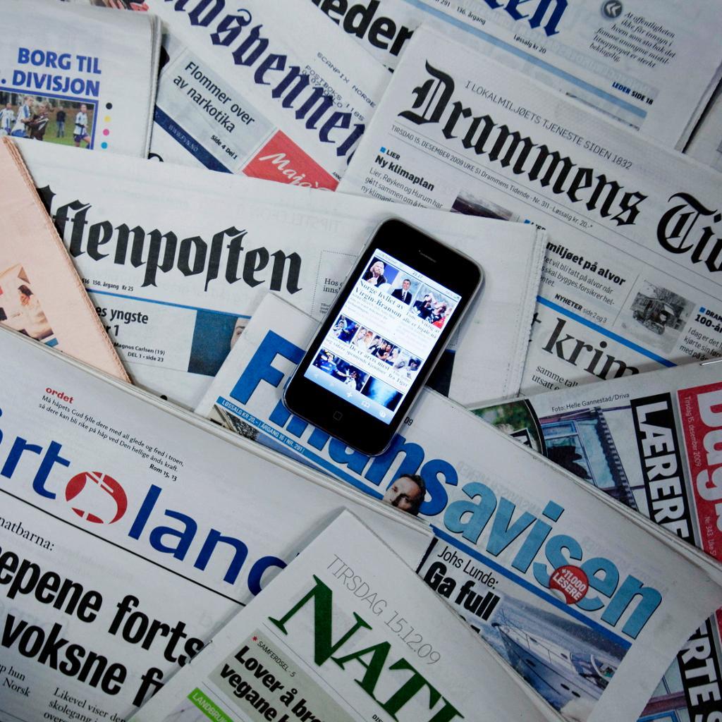 Mobiltelefon som ligg oppå fleire aviser. Foto.