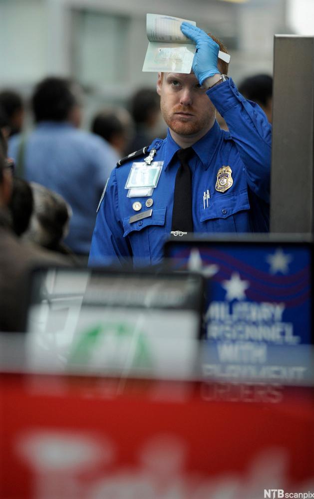 Tollbetjent holder opp et dokument. foto.
