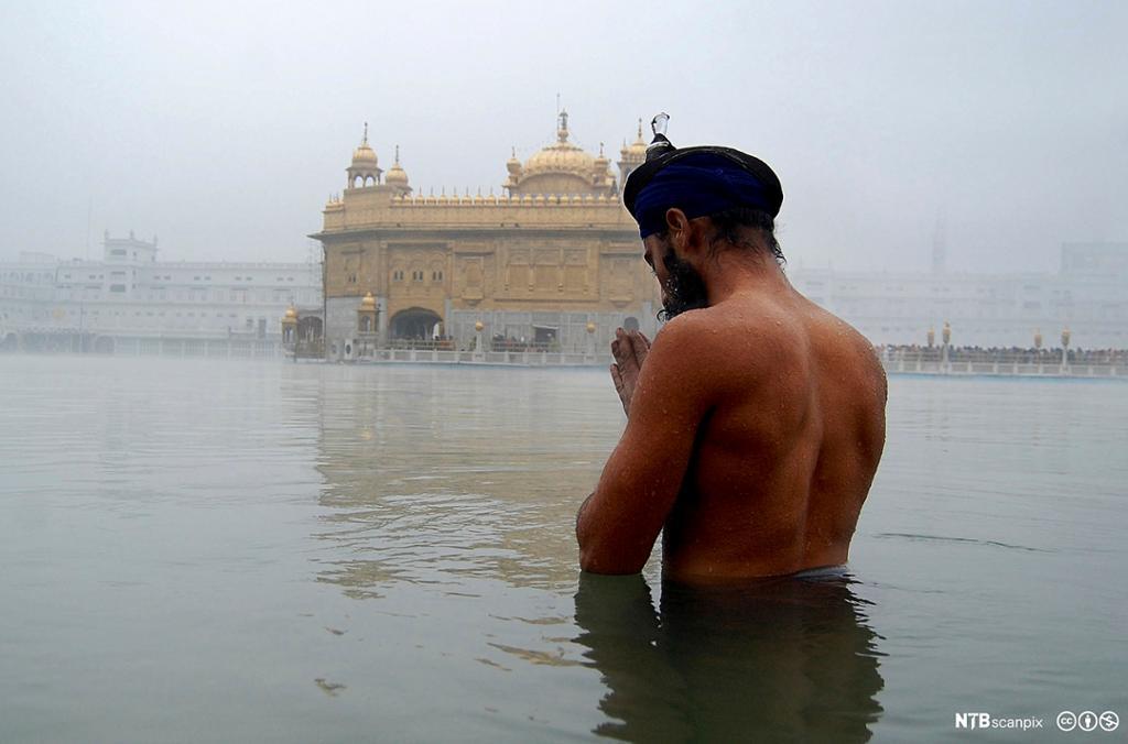 En mann står til livet i vann med turban på hodet og ber. I bakgrunnet et tempel. Foto.