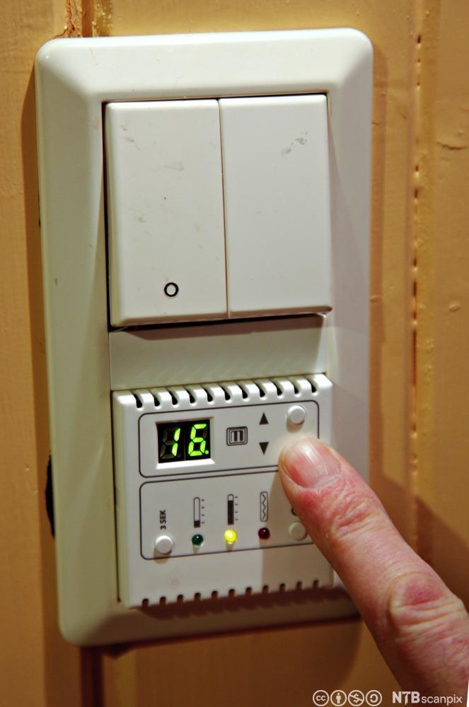 Finger som regulerer termostat. Foto.
