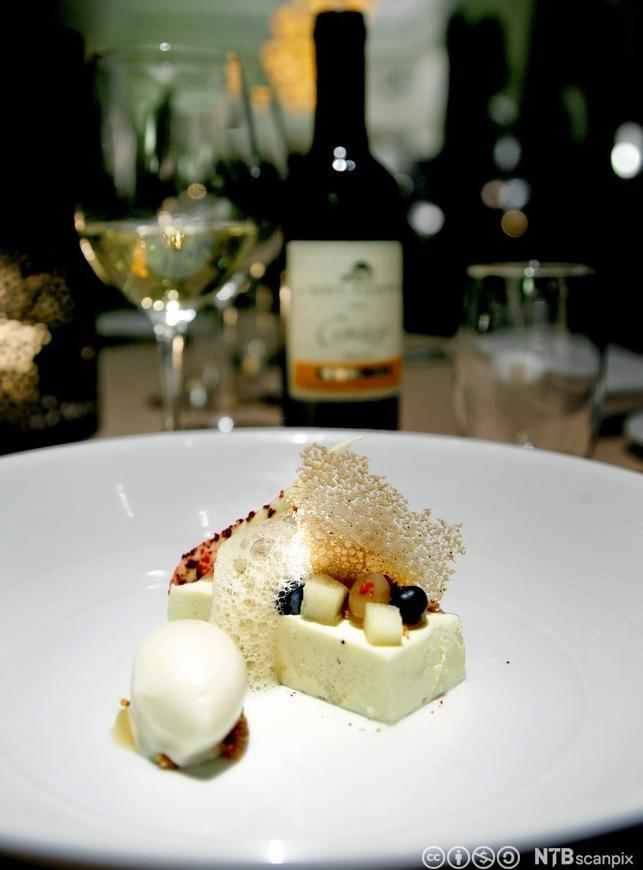 Bilete av ein tallerken med dessert og ei flaske med dessertvin i bakgrunnen. Foto.