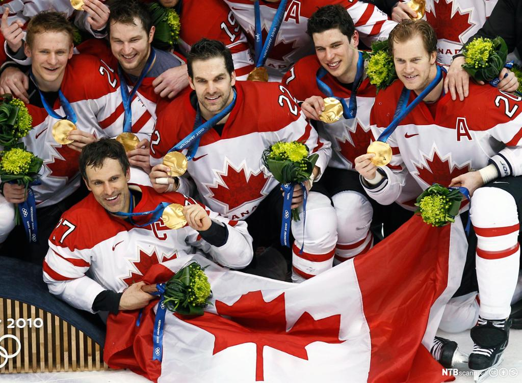 The Canadian men's hockey team pose with their gold medals at the Vancouver 2010 Winter Olympics