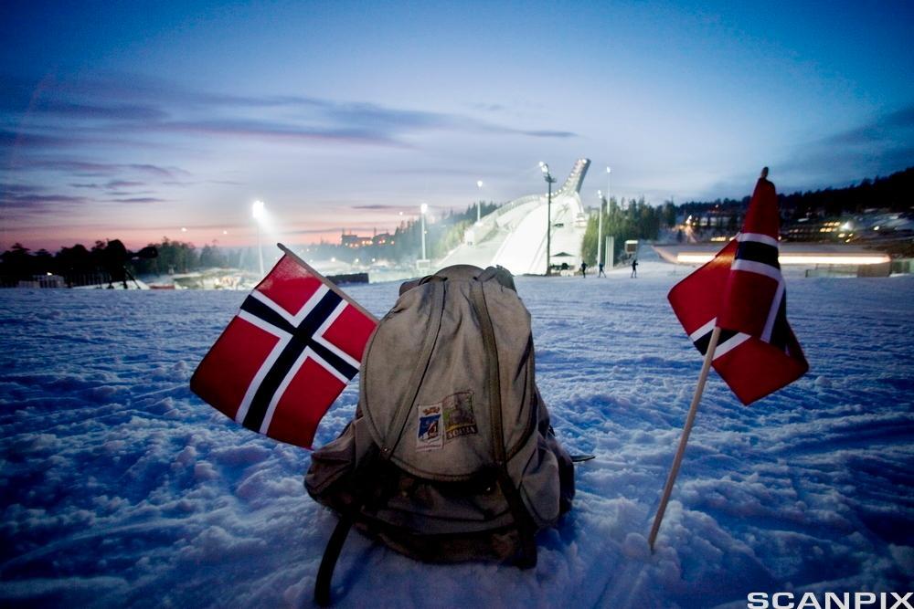 Gammel ryggsekk med norske flagg og Holmekollbakken i bakgrunnen. Foto.