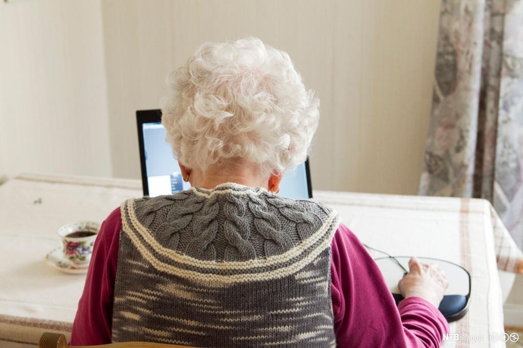 Eldre kvinne sitter ved datamaskin. Foto.