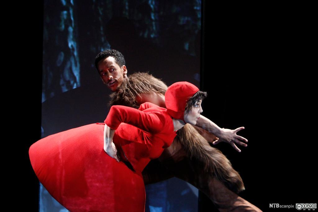 Kvinne i rød kjole og rød hette og mann i ulvekostyme danser. Foto.