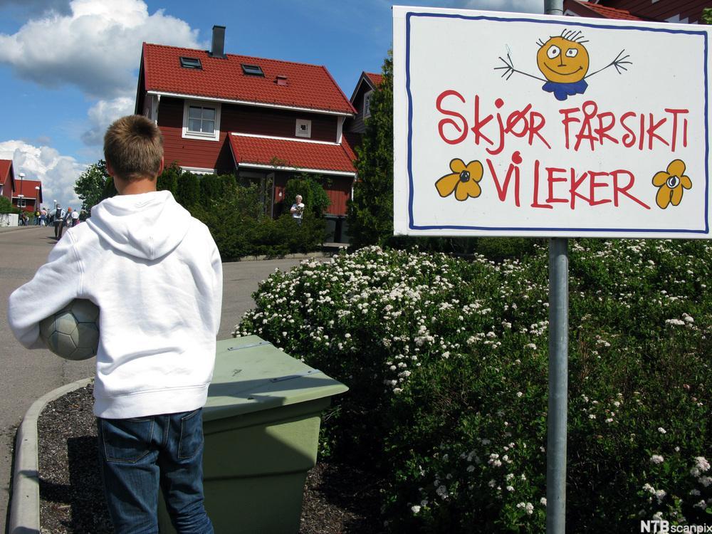 Gutt står med ryggen til ved siden av et skilt med tydelige skrivefeil. Foto