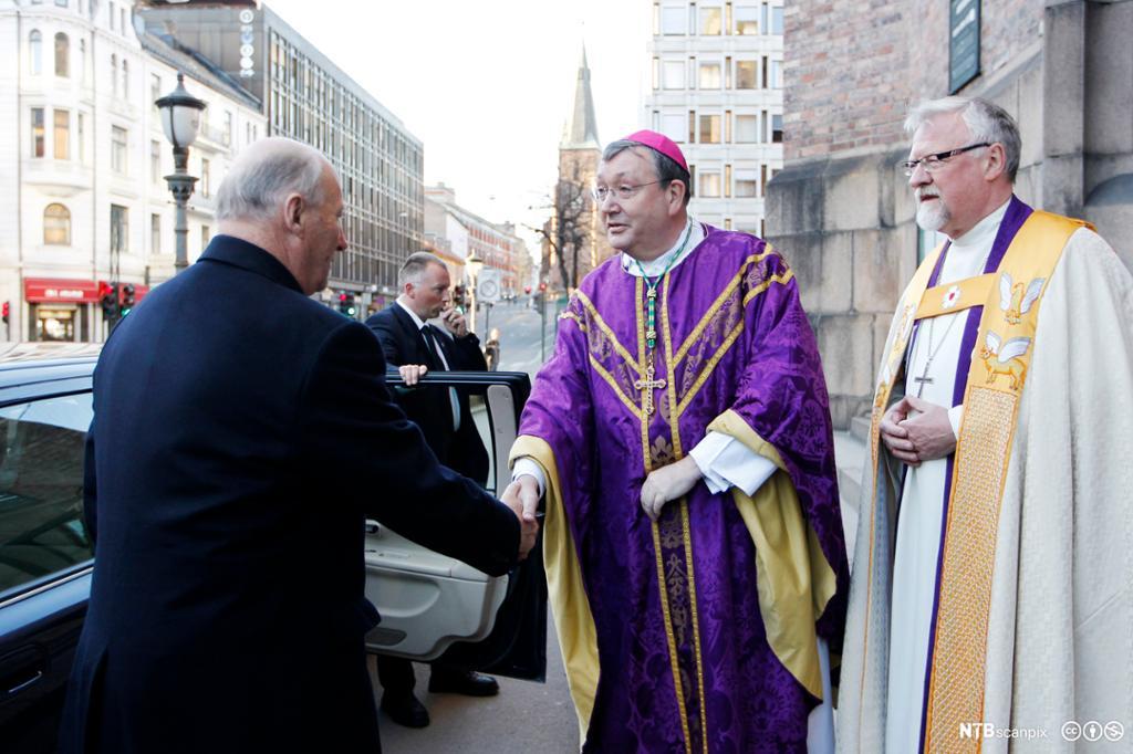 To biskoper kledd i kjortel og messehagel hilser på en mann i frakk. Foto.