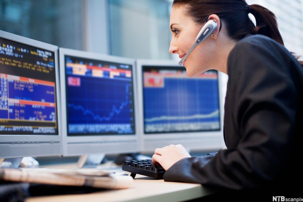 Kvinne med hodemikrofon som sitter foran tre skjermer fulle av innhold. Foto.