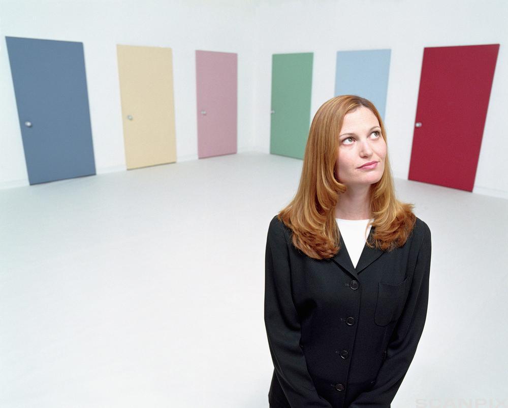 undrende dame foran fargerike dører. Foto.