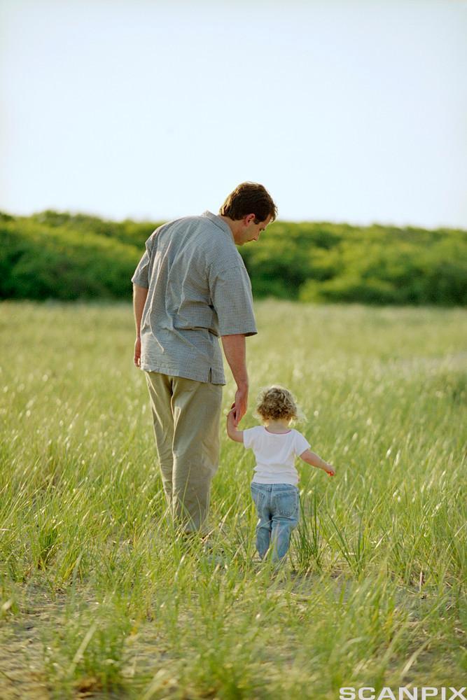 Mann går med barn. Foto.
