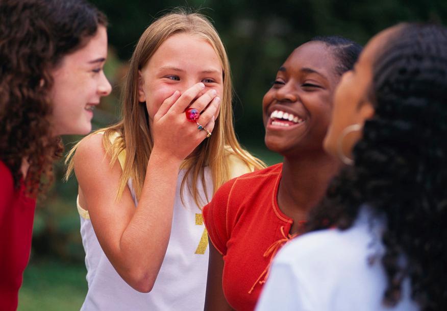 4 jenter som står saman i ein ring og ler. Foto.
