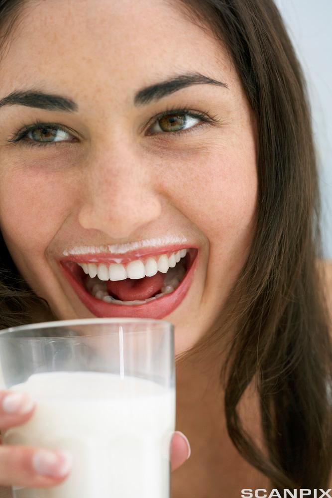 Kvinne drikker melk. Foto.