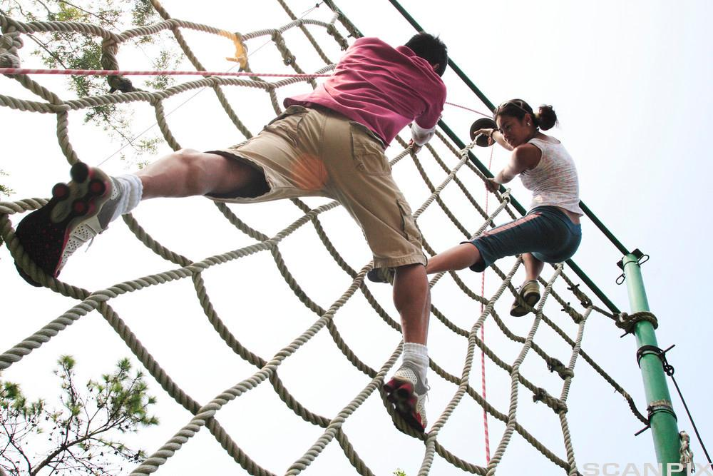 Ungdom i klatretauvegg. Foto.