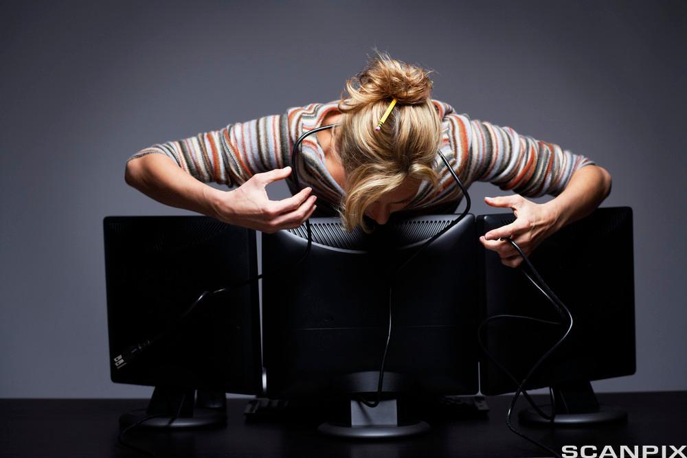 Kvinne som står fremover lent over tre dataskjermer og virker fortvilet. Foto