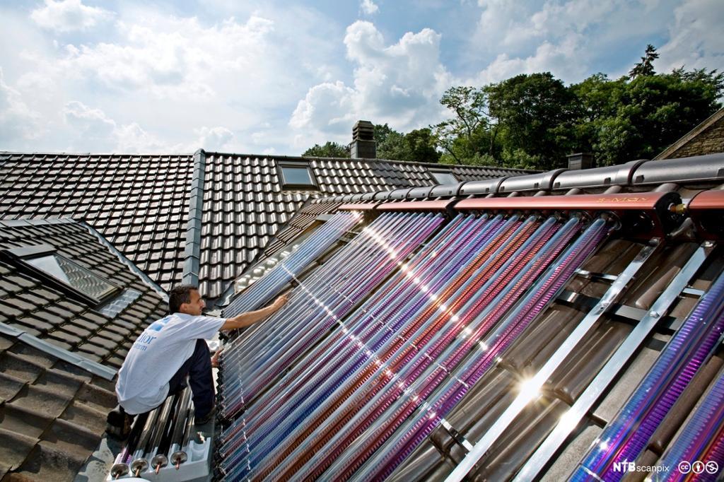 Mann installerer solfanger på tak. Foto.
