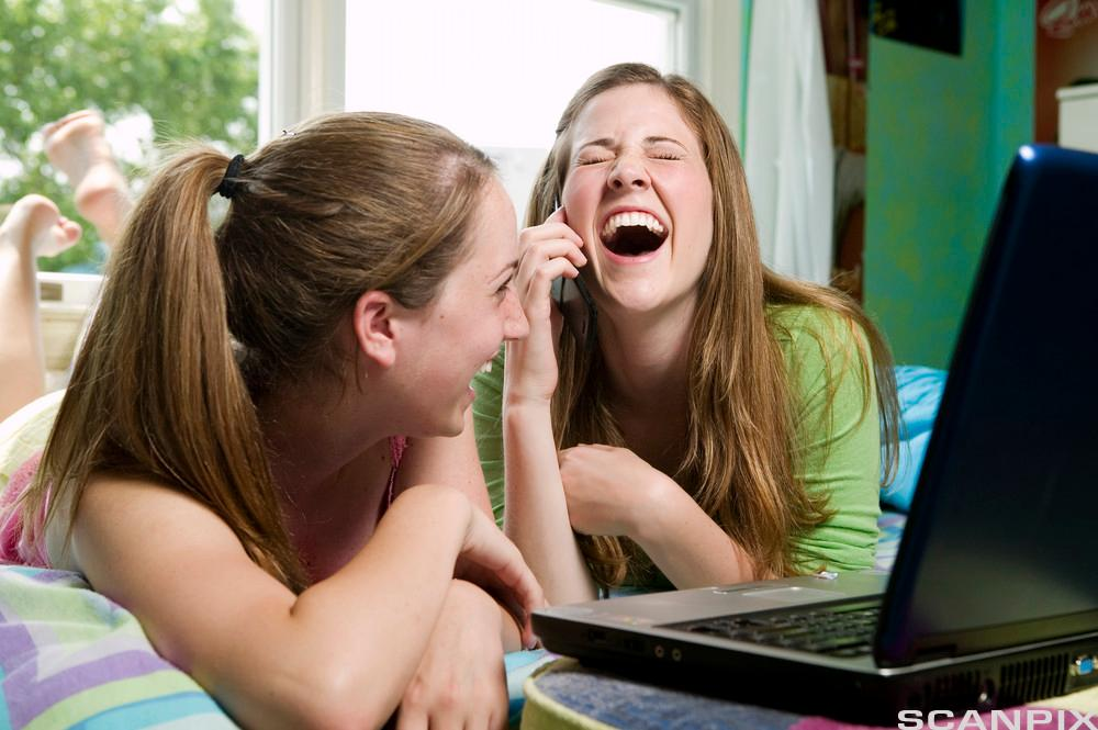 To jenter som ler foran en PC. Foto.