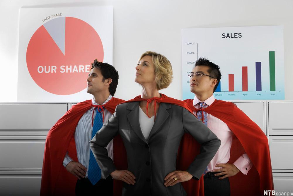 BIlde av tre selgere med rød kappe med salgsplansjer i bakgrunnen.