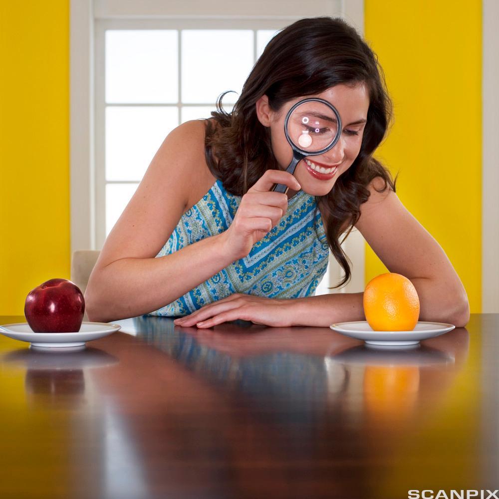 Kvinne undersøker frukt med forstørrelsesglass. Foto.