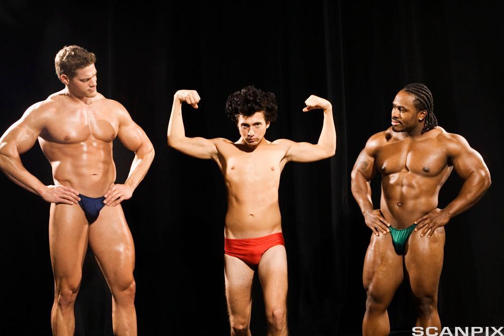 En spinkel mann spenner overarmsmusklene mellom to bodybuildere som ser på. Foto.