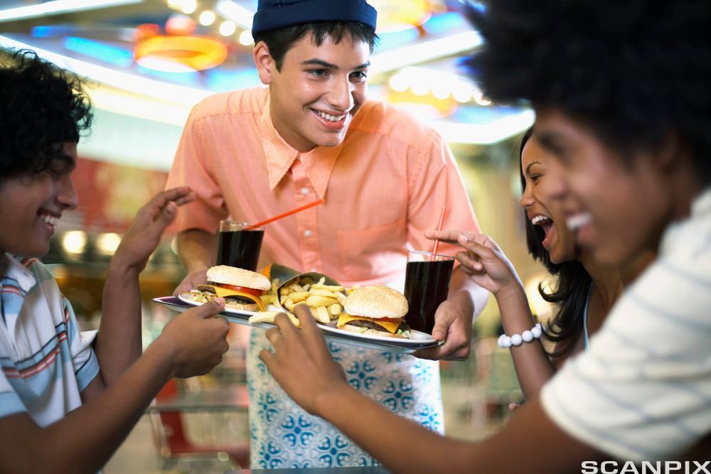 Kelner serverer middag. Foto.