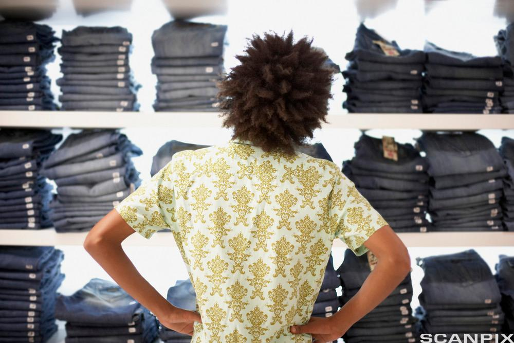Ung mann kjøper jeans. Foto.