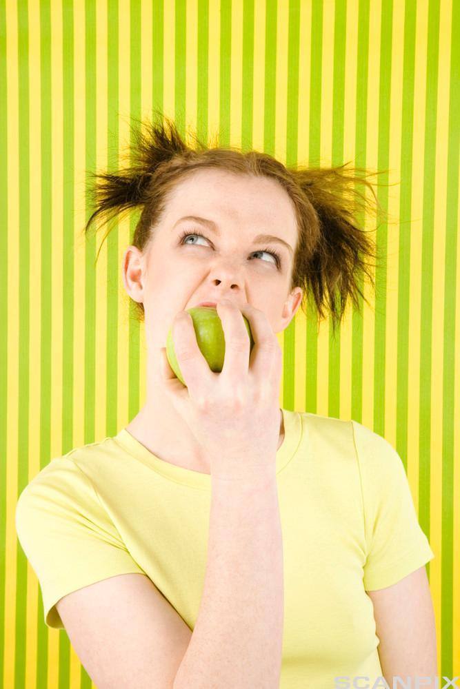 En jente spiser et eple. Foto.