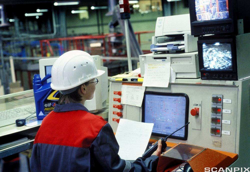 Arbeider overvåker produksjonslinje. foto.