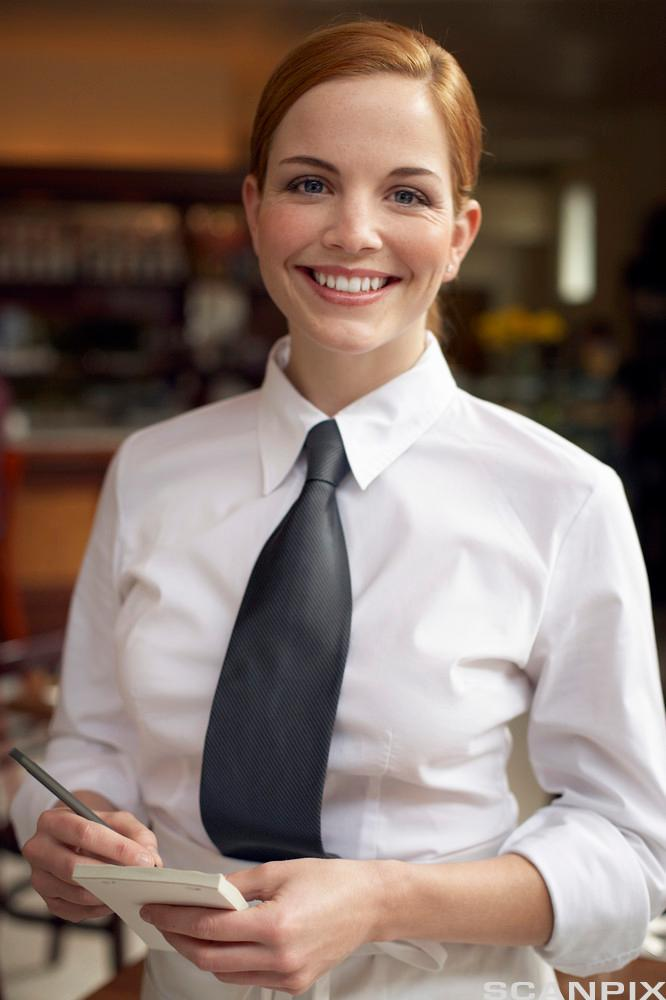 Blid kelner med hvit skjorte og svart slips og notatblokk. Foto.