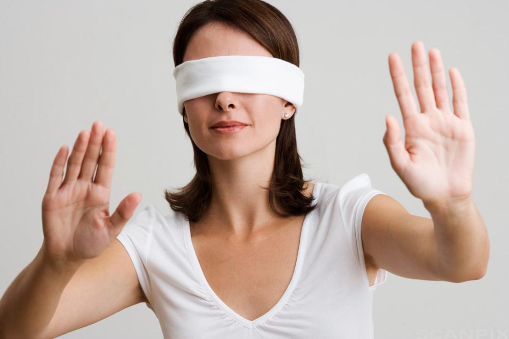 Dame med bind foran øynene. Foto.
